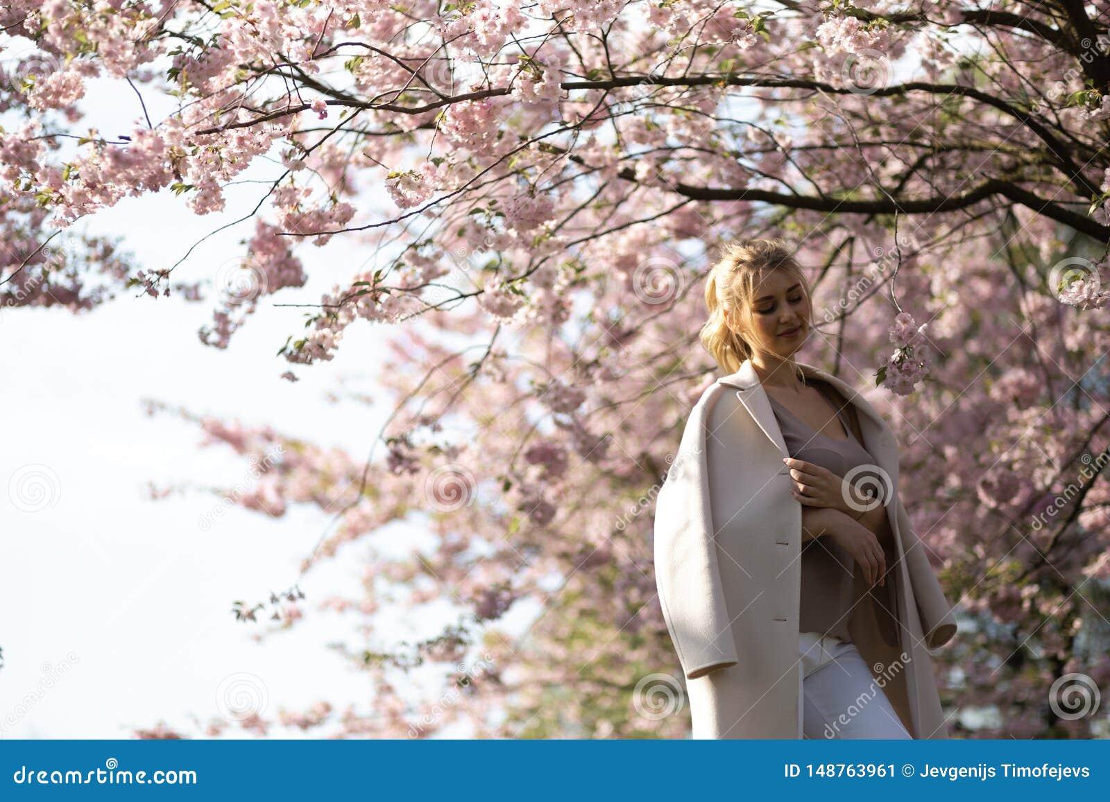 Mujer joven rubia hermosa en el parque de Sakura Cherry Blossom en primavera que disfruta de la naturaleza y del tiempo libre dur