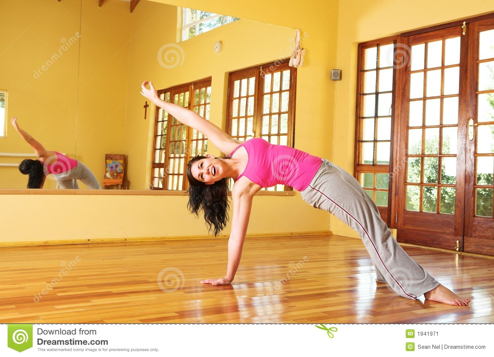 Mujer joven sana en estirar del equipo de la gimnasia