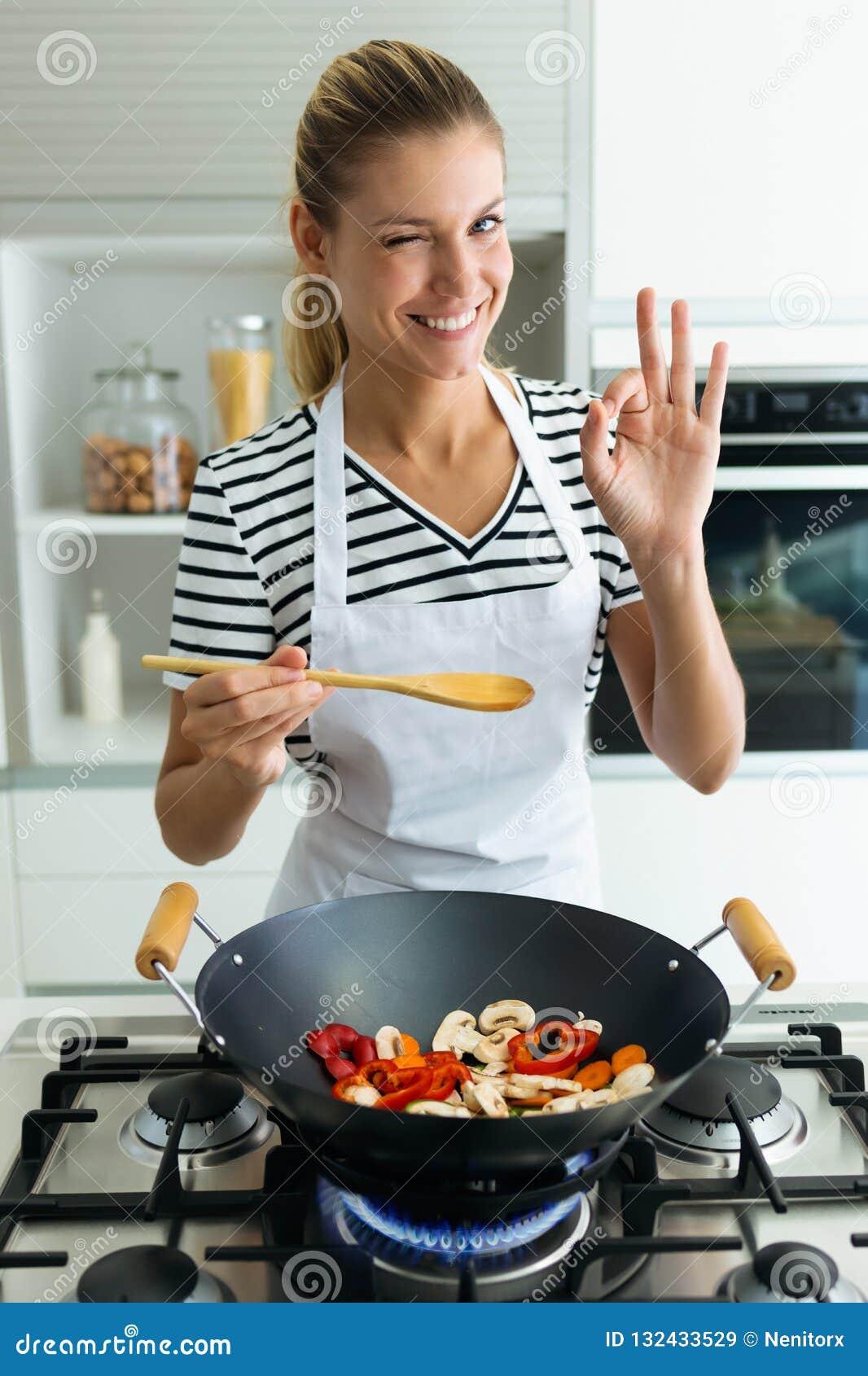 Mujer joven sana que mira la cámara mientras que cocina y mezcla la comida en sartén en la cocina en casa
