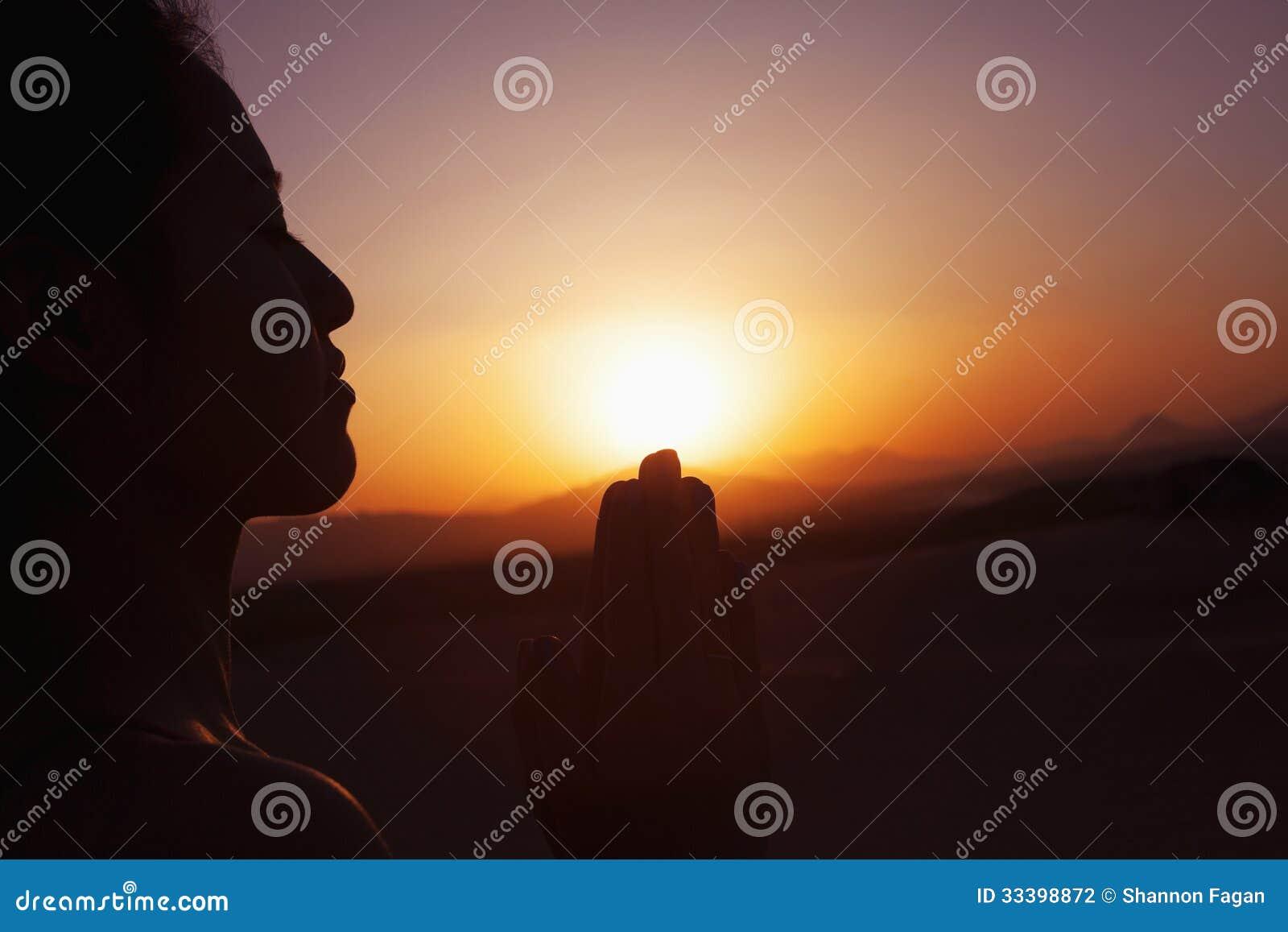 Mujer joven serena con las manos junto en actitud del rezo en el desierto en China, silueta, ajuste del sol