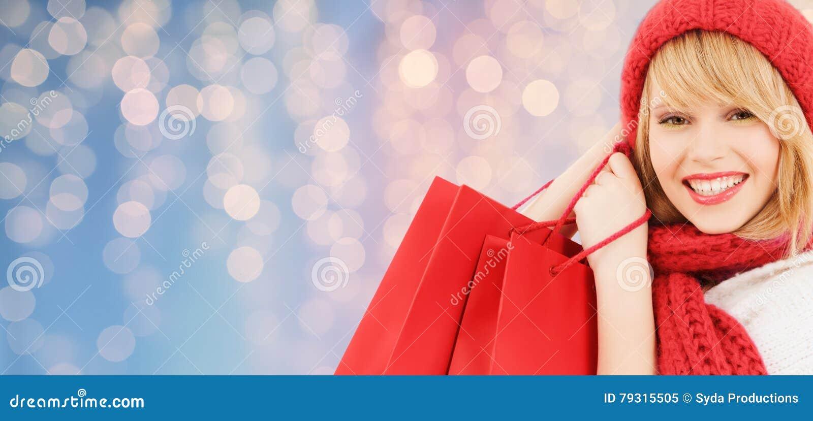 Mujer joven sonriente con los bolsos de compras