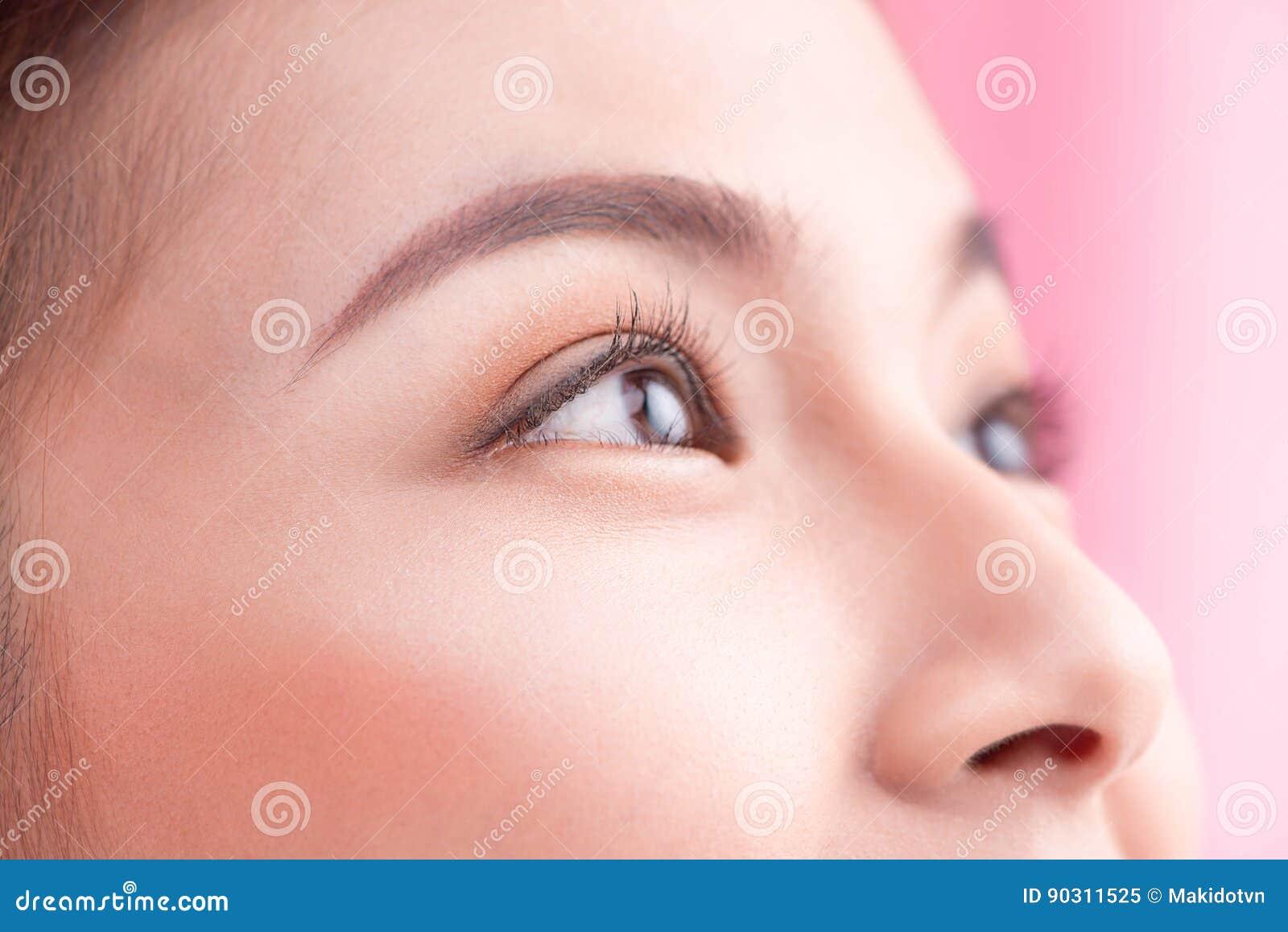 Mujer joven sonriente con los dientes sanos que sostienen un cepillo de  dientes sobre fondo rosado f30f2f853fb9
