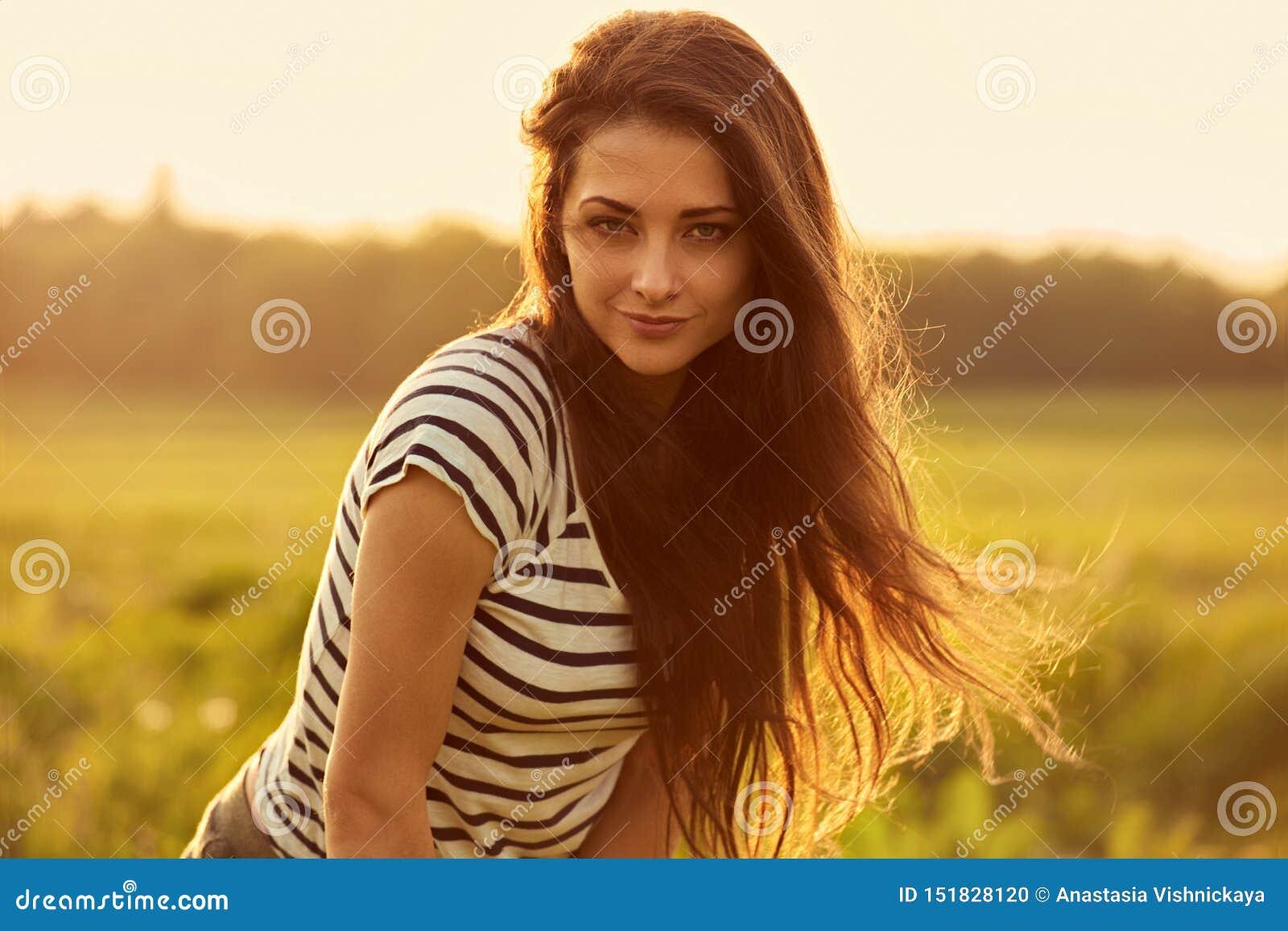 Mujer joven sonriente de pensamiento hermosa que parece feliz con el pelo brillante largo en fondo del verano de la puesta del so