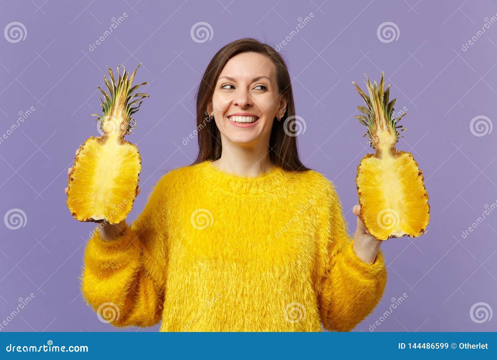 Mujer joven sonriente en el suéter de la piel que mira a un lado que lleva a cabo halfs de la fruta madura fresca de la piña aisl