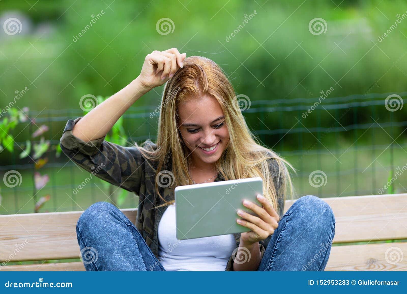 Mujer joven sonriente feliz que rasguña su cabeza