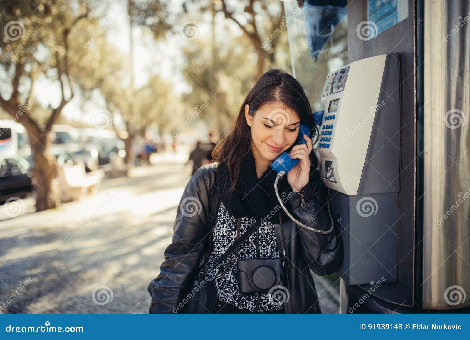 Mujer joven sonriente que habla en su smartphone en la calle Comunicando con los amigos, libere las llamadas y los mensajes para