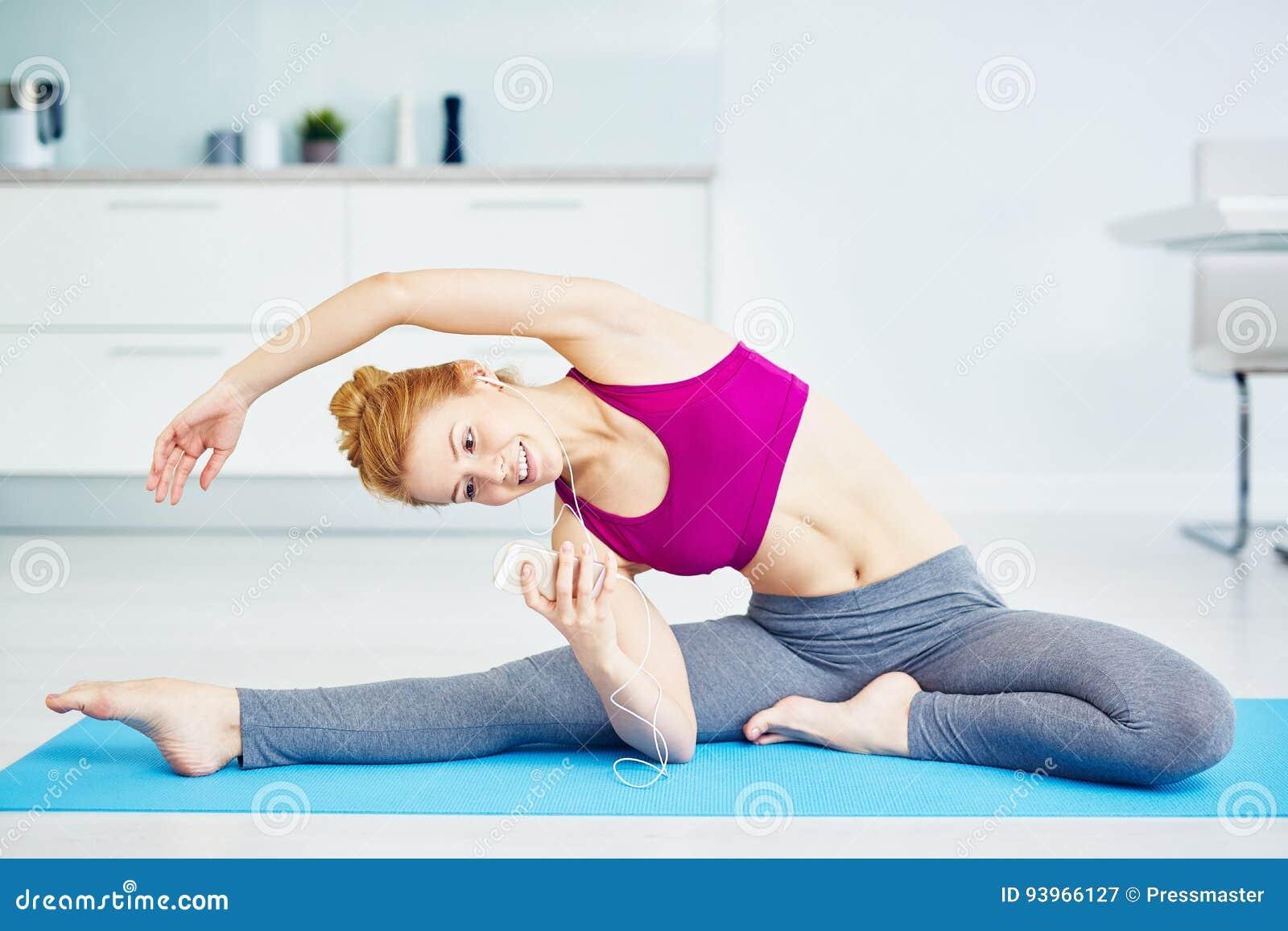 Mujer joven sonriente que hace estirando ejercicios