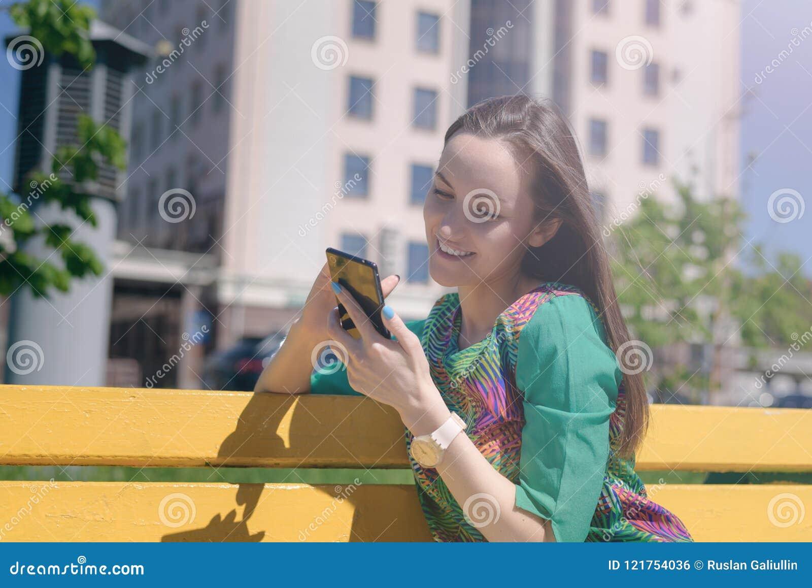 Mujer joven sonriente que se sienta en un banco amarillo y usar el smartphone, comunicación en línea, redes sociales, corresponde