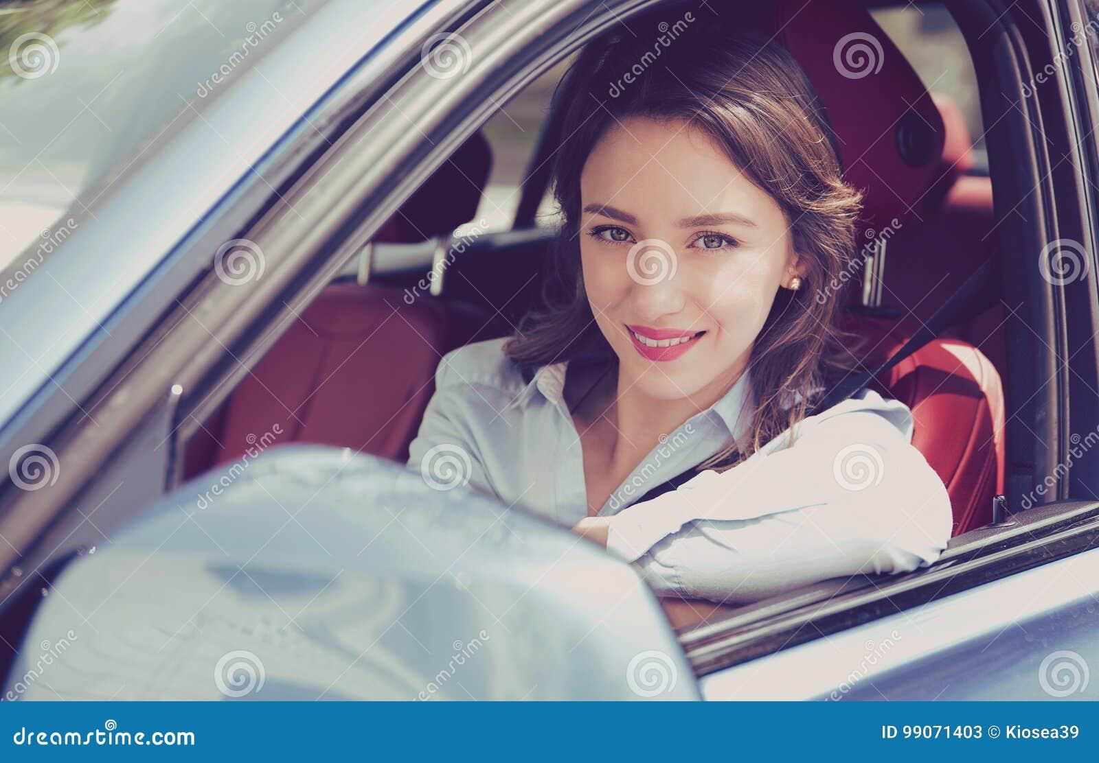 Mujer joven sonriente que se sienta en un coche