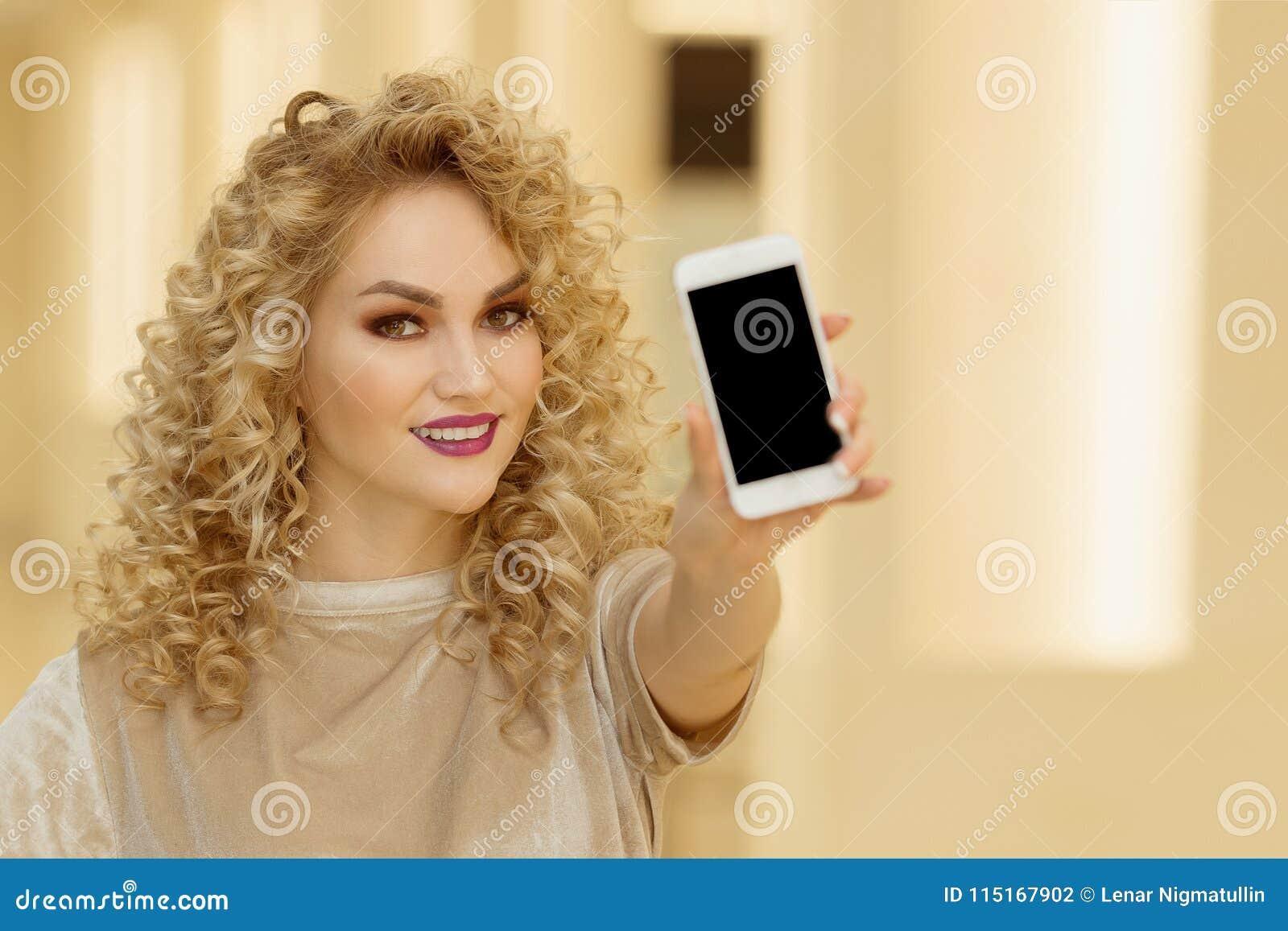 Mujer joven sonriente que sostiene el teléfono móvil en la alameda