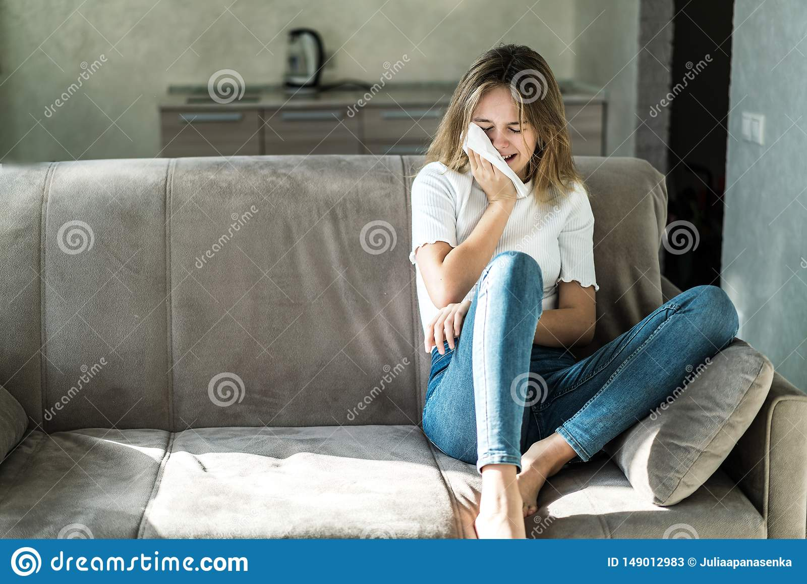Mujer joven triste que se sienta en el sof? en casa y el griter?o