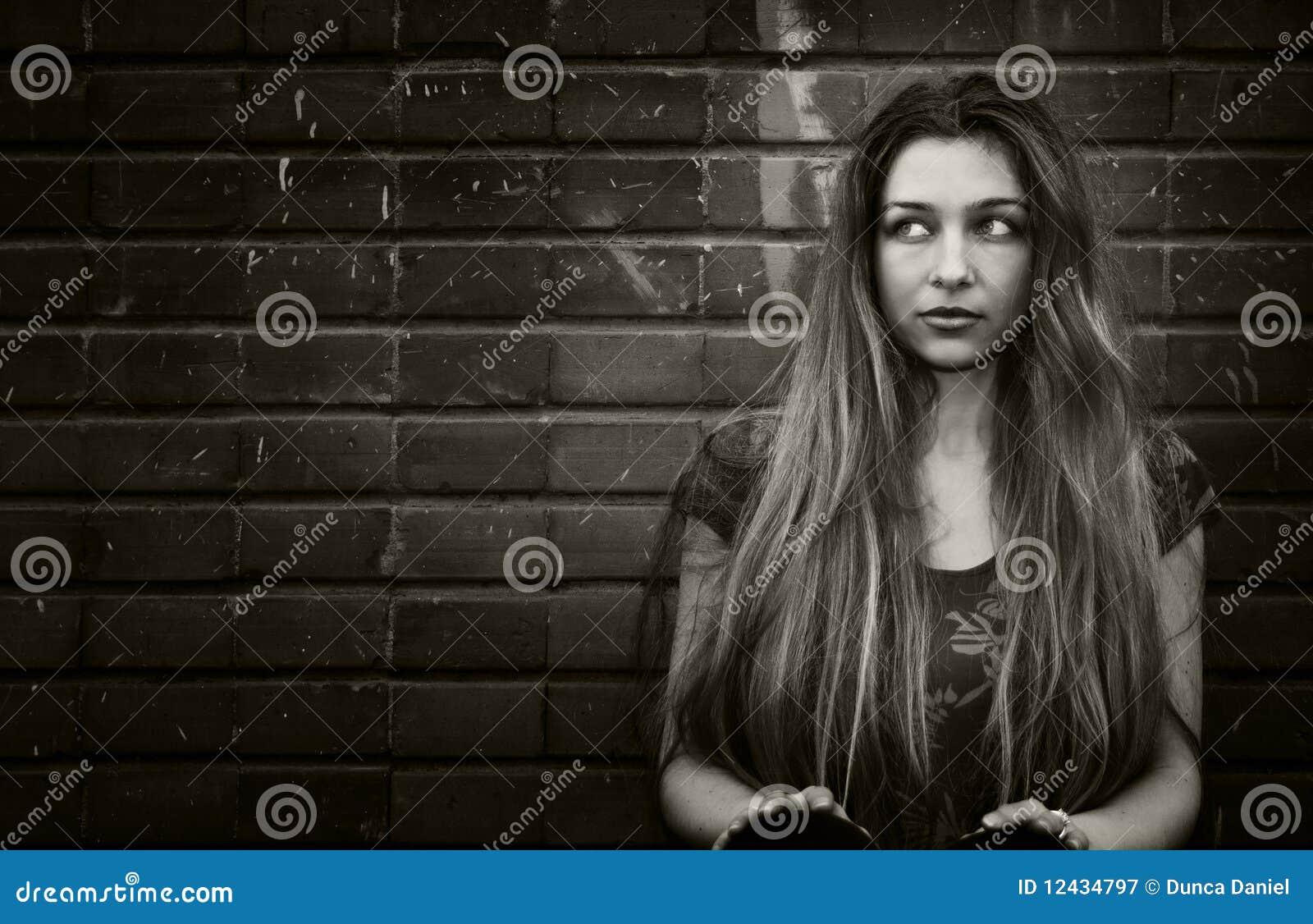 Mujer joven urbana que se sienta cerca de la pared de ladrillo