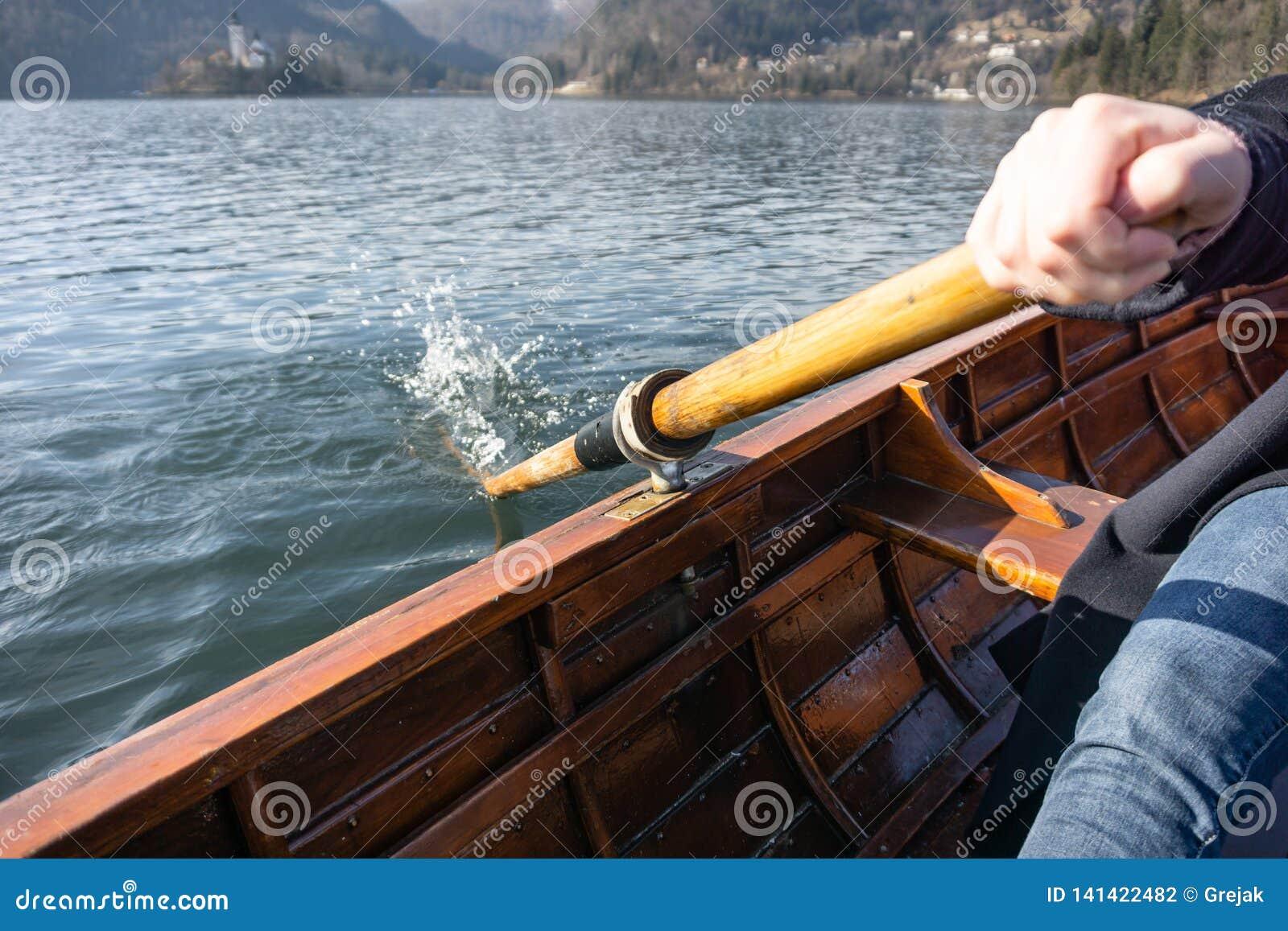 Mujer joven usando la paleta en un barco de madera con la isla sangrada detrás de ella - Eslovenia sangrada lago que rema en los