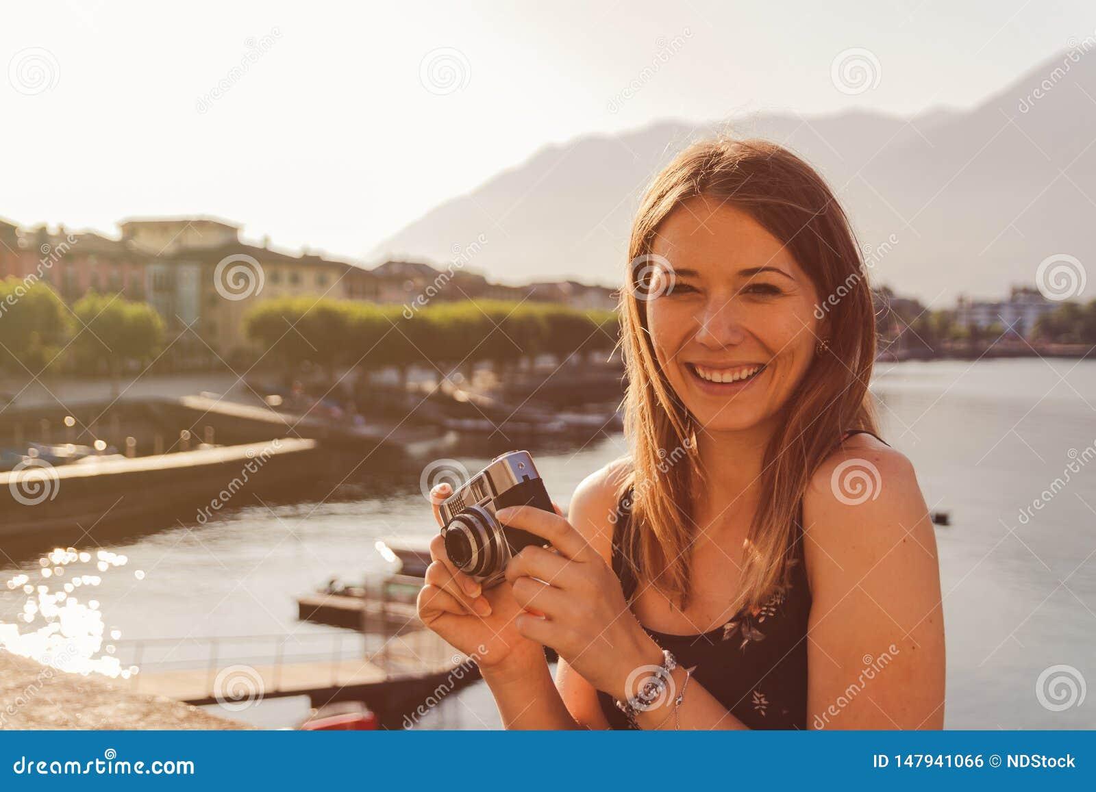 Mujer joven usando una c?mara del vintage delante de la  promenade  del lago en Ascona