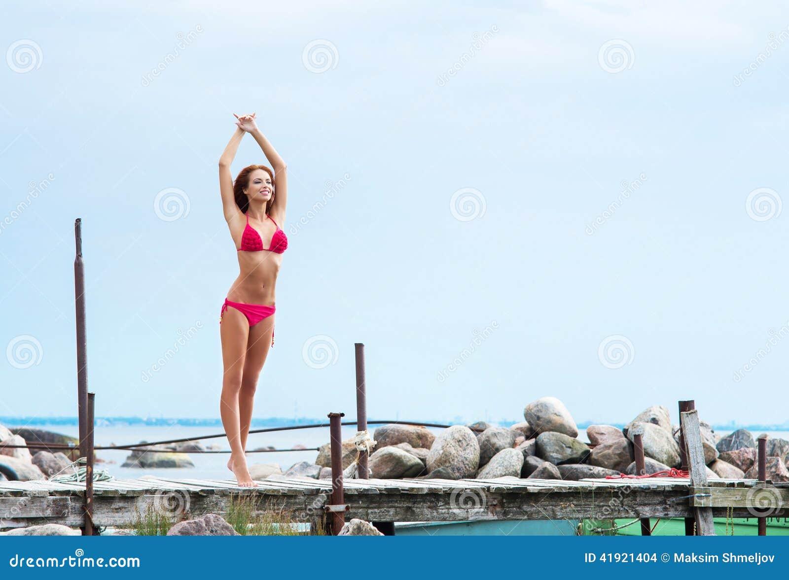 Mujer joven y atractiva del pelirrojo que se relaja en el embarcadero