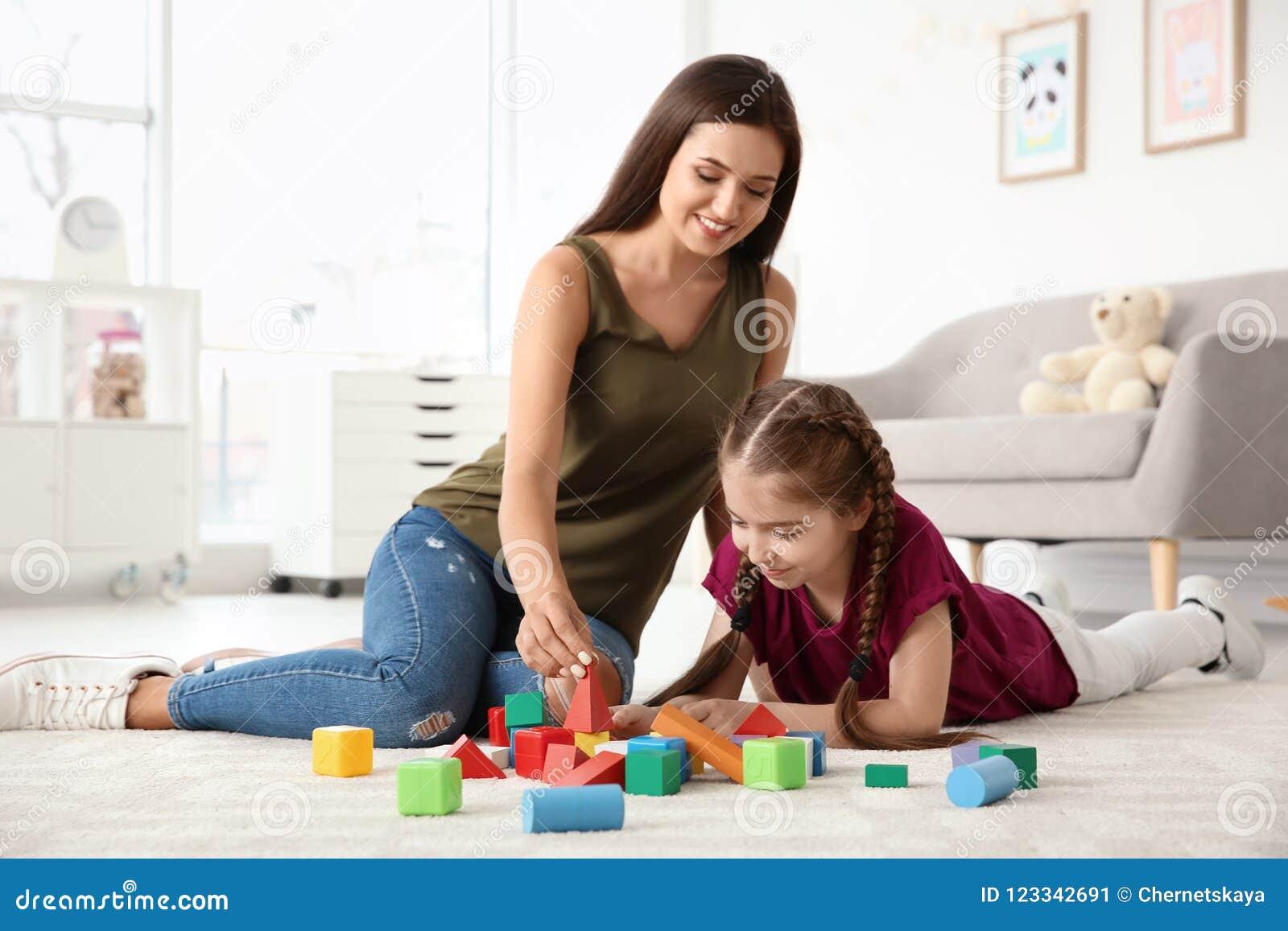 Mujer joven y niña con jugar autístico del desorden