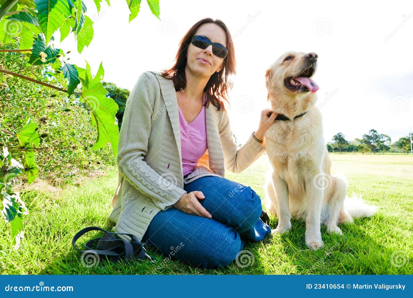 Mujer joven y perro perdiguero de oro que se sientan en hierba 