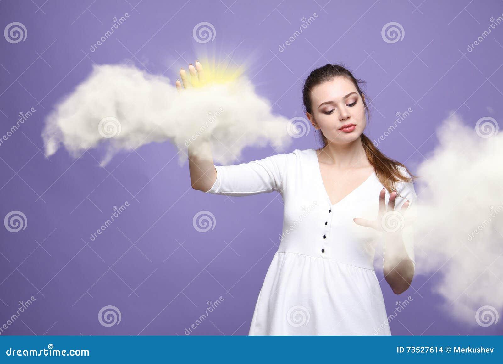 Mujer joven y sol que brillan hacia fuera de detrás las nubes, la computación de la nube o el concepto del tiempo