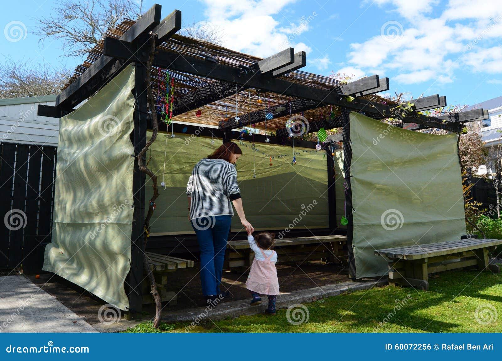 Mujer judía y niño que visitan a su familia Sukkah