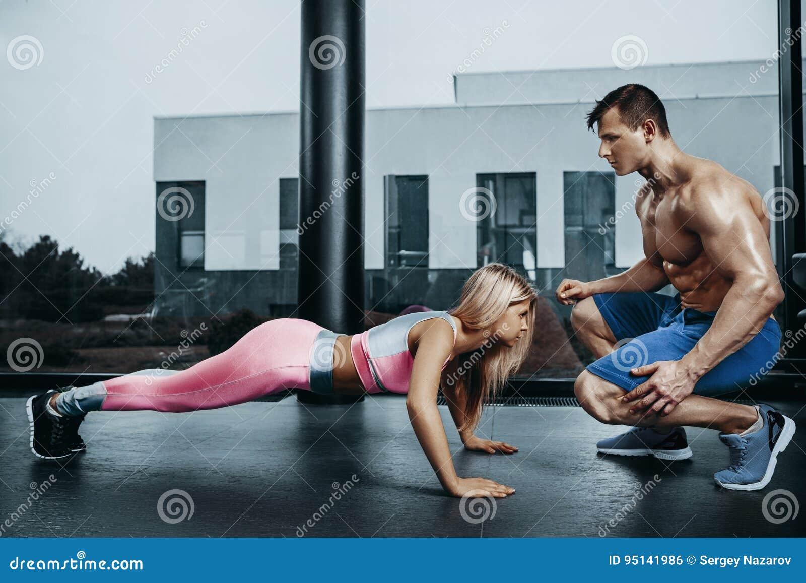 Mujer juguetona que hace el ejercicio del tablón que entrena detrás y los músculos de la prensa con el instructor Poder de la fue