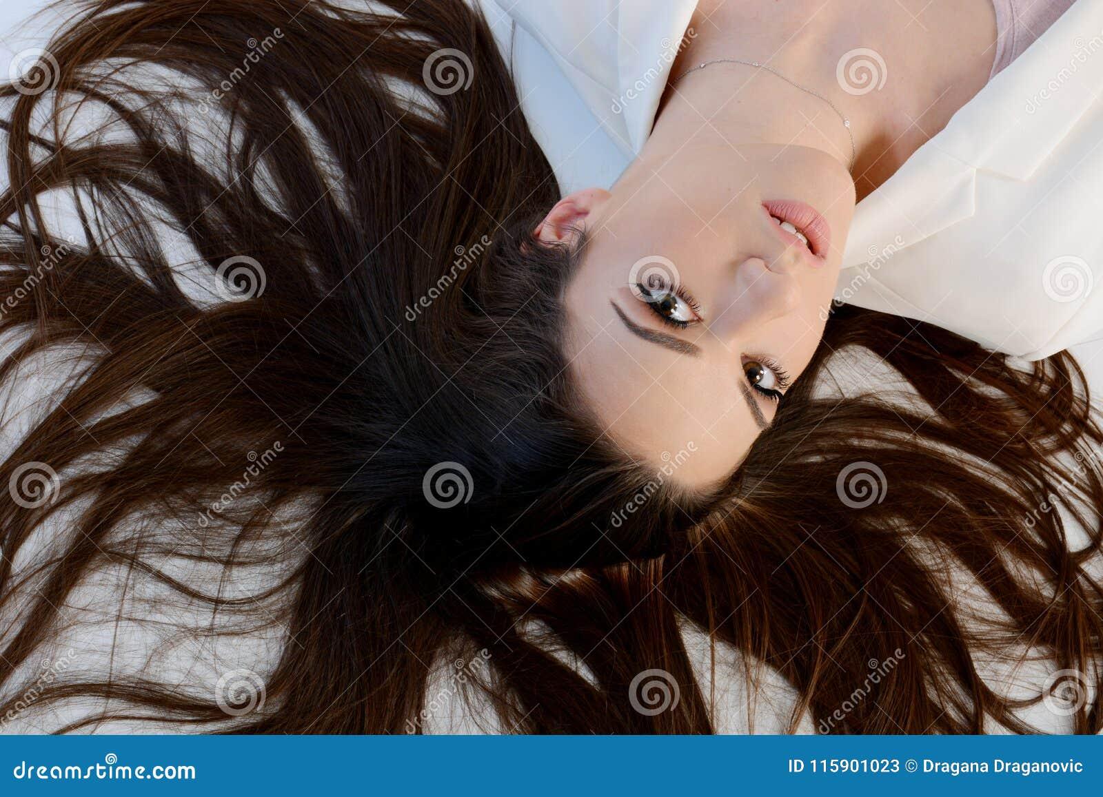 Mujer larga hermosa del pelo que pone en piso
