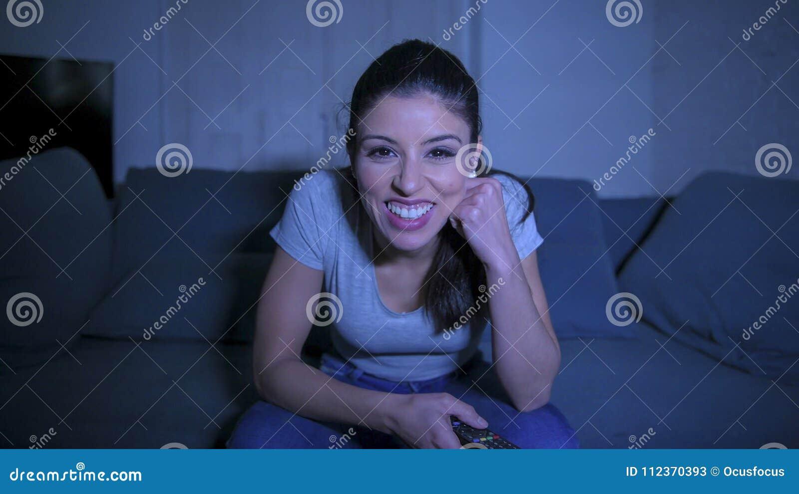 Mujer latina hermosa y feliz joven en su 30s que sostiene el telecontrol de la TV que disfruta en casa del programa de televisión