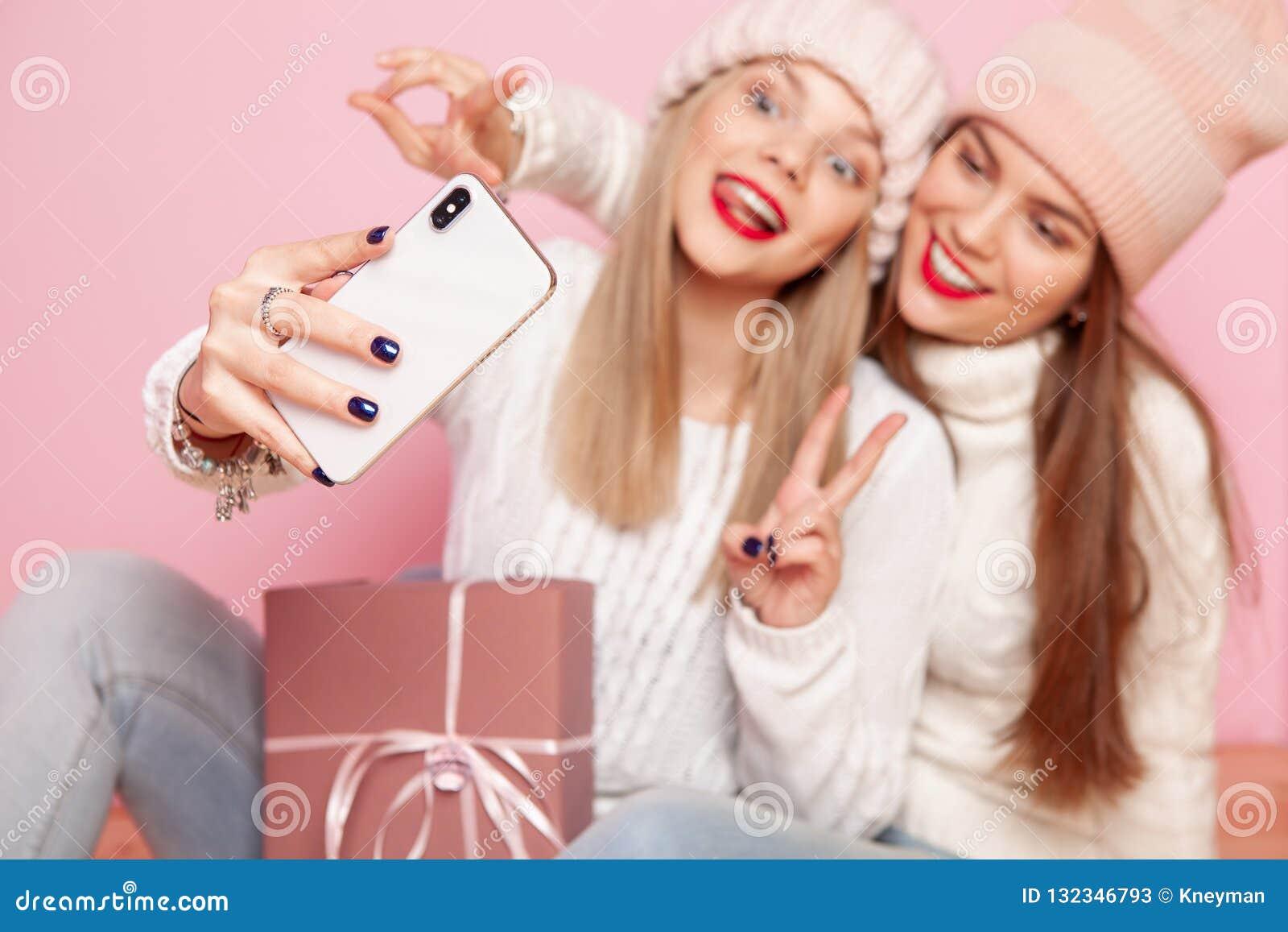 13e0c6d374e0d Dos mujeres lindas con los labios rojos y los sombreros que comparten el  regalo entre ellos mismos Fabricación del selfie por smartphone La Navidad  del ...