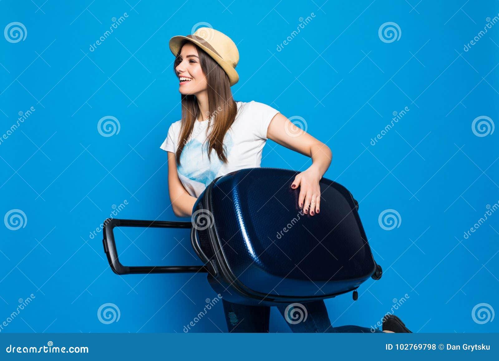 Mujer lista para el viaje del verano aislado en fondo azul Mujer bonita que corre con equipaje en fondo azul