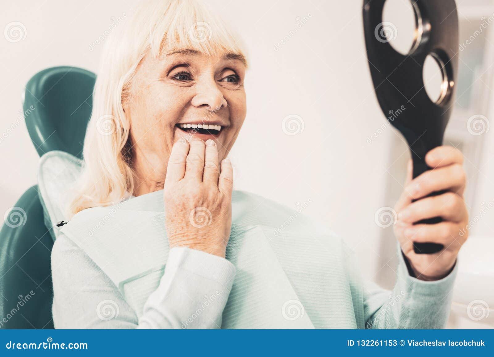 Mujer madura con el espejo que mira su dentadura