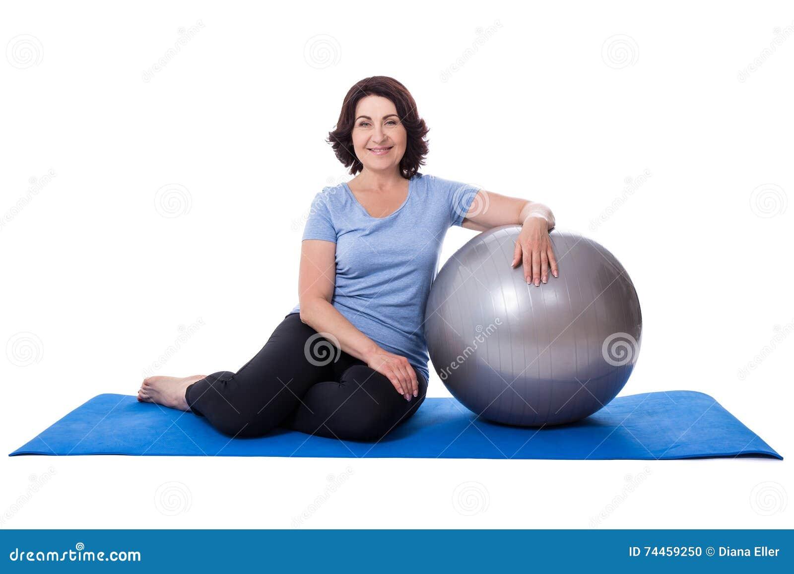 Mujer madura feliz que se sienta en la estera de la yoga con la bola de la  aptitud aislada en el fondo blanco 732d77ef9ac0