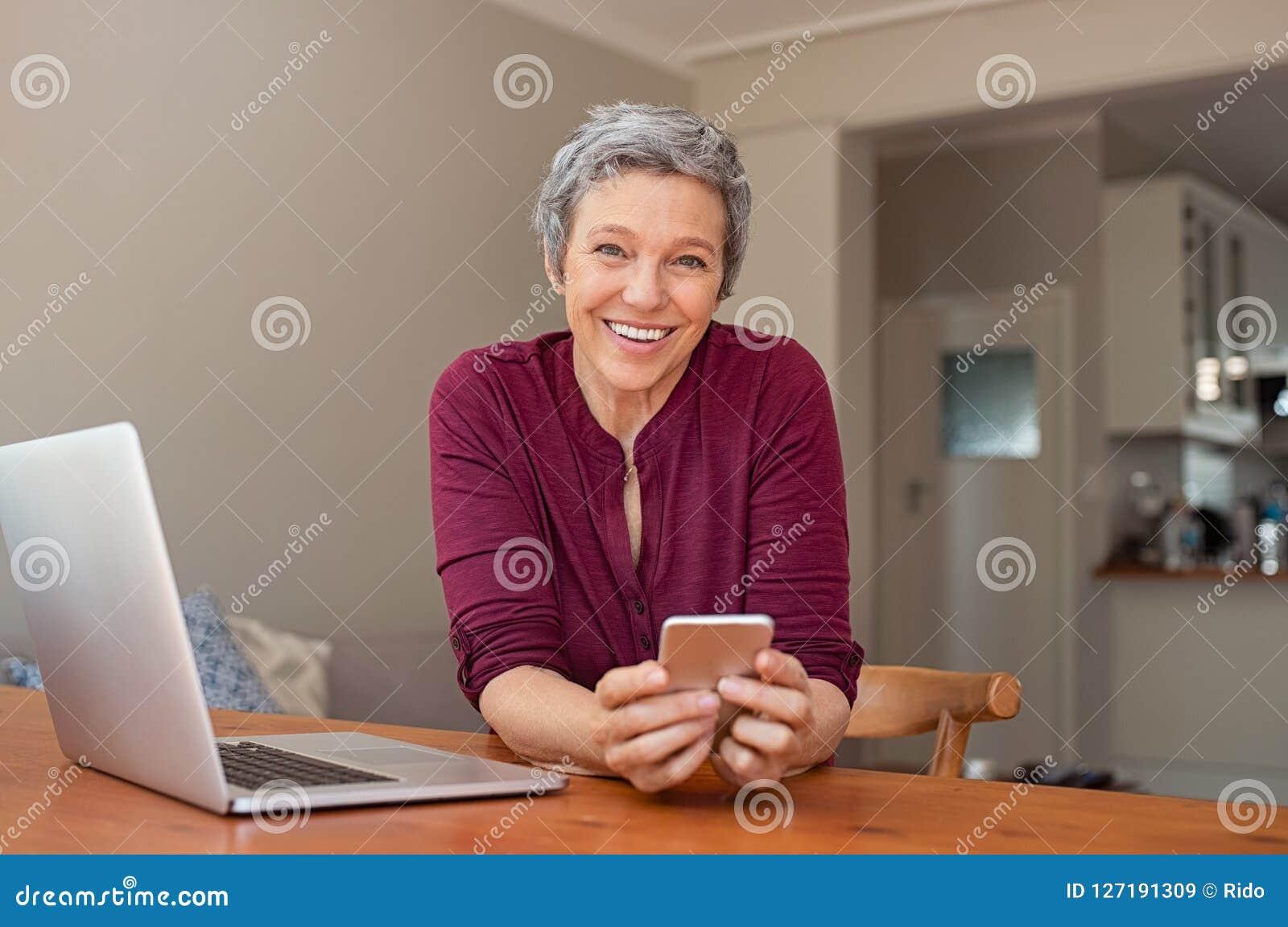 Mujer madura feliz que usa smartphone