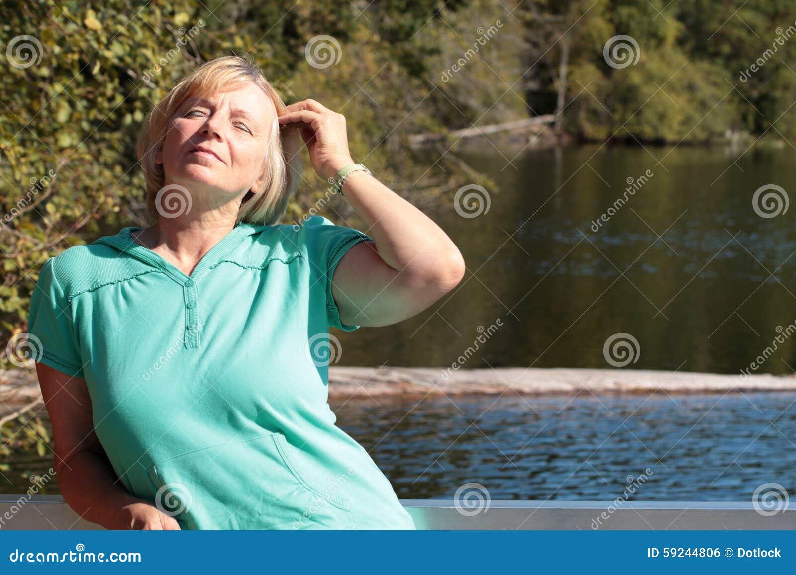 Mujer madura que goza del sol en naturaleza