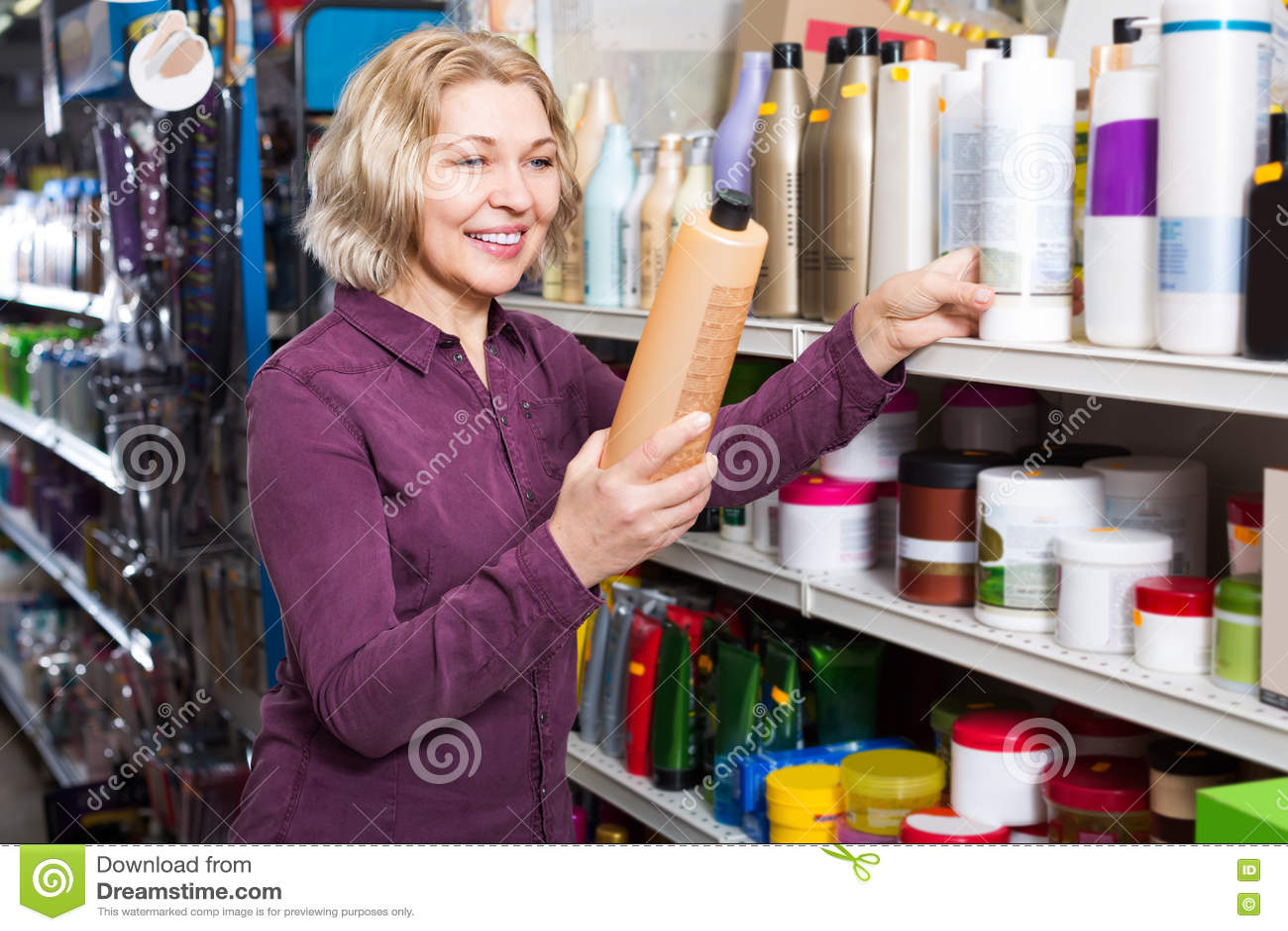 Mujer madura que selecciona champú en tienda