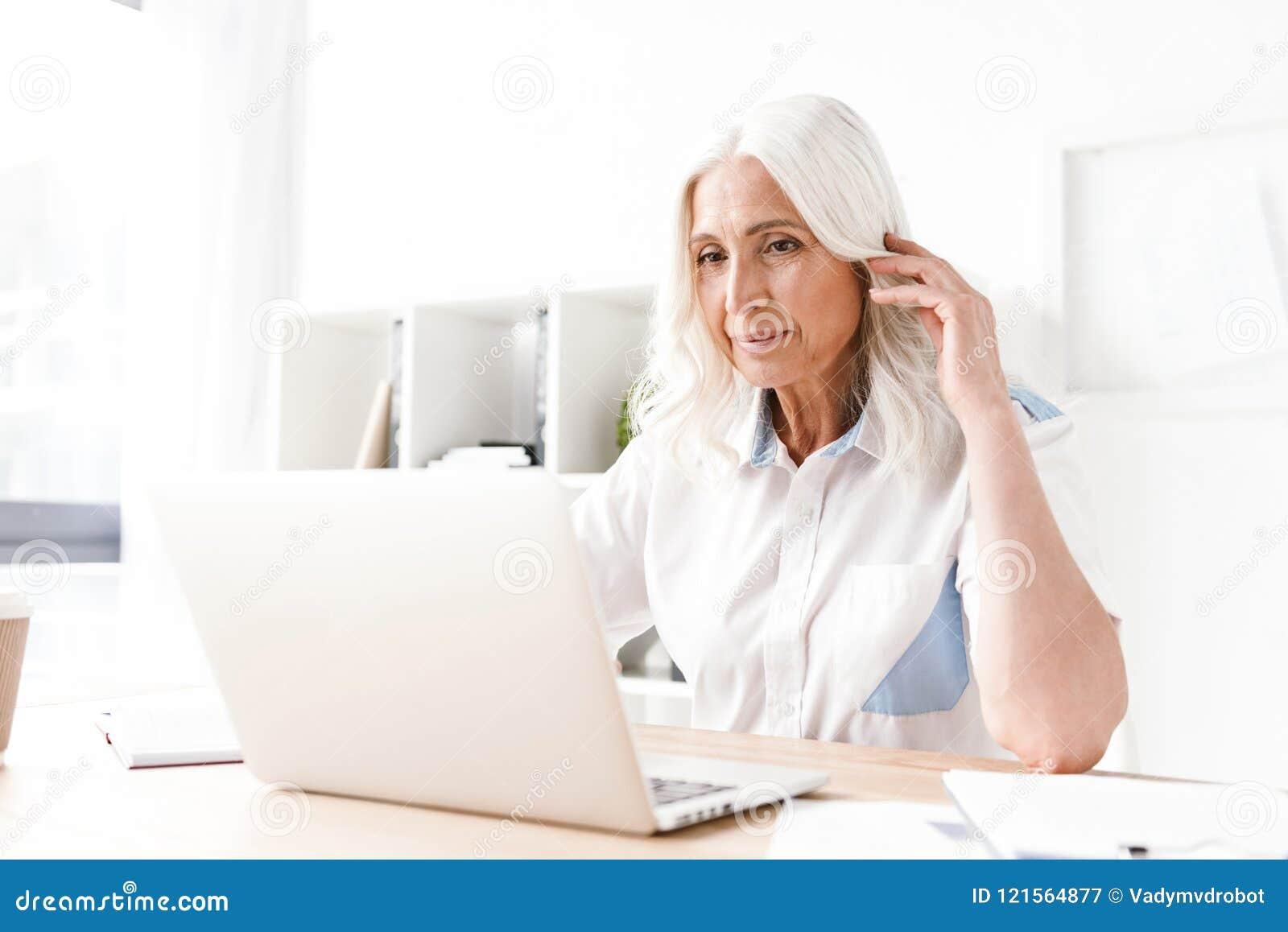 Mujer madura seria que se sienta dentro en el funcionamiento de la oficina