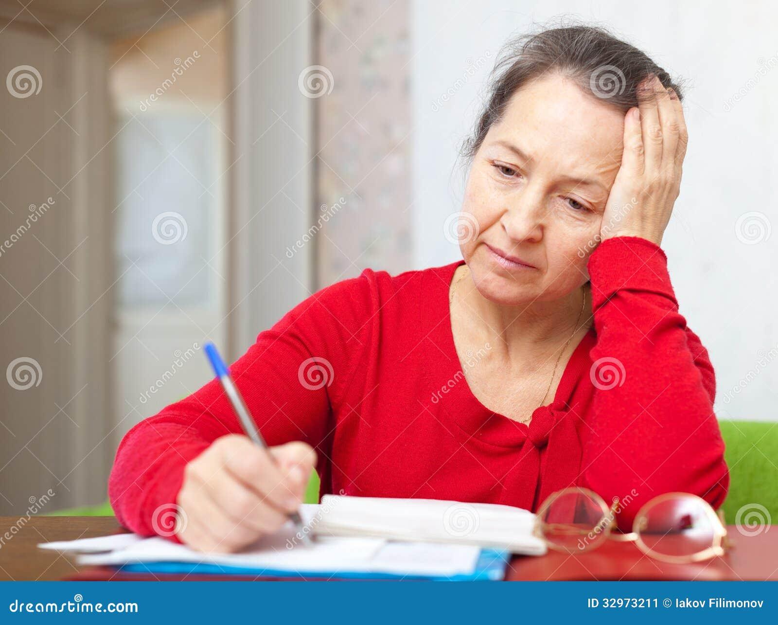 Mujer madura triste con las facturas de servicios públicos