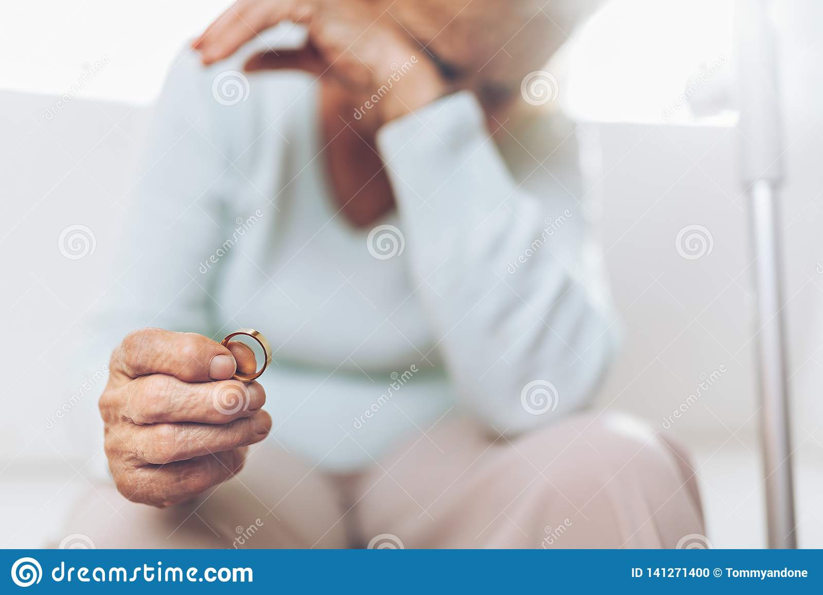 Mujer mayor afligida que lleva a cabo un anillo de bodas