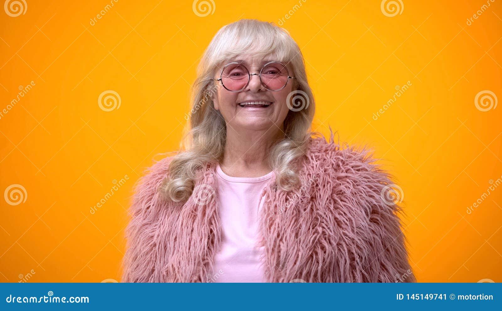 Mujer mayor alegre en capa rosada y gafas de sol redondas que sonríe en cámara