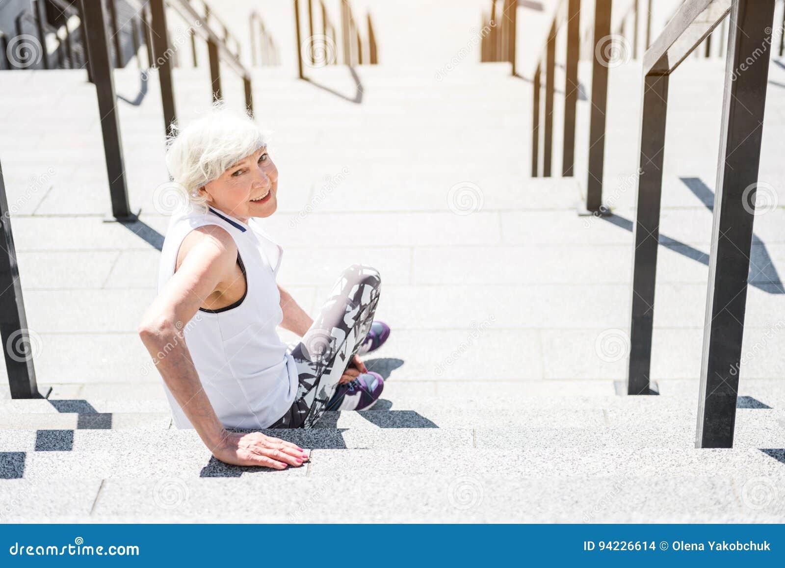 Mujer mayor alegre que se relaja después de entrenar en las escaleras