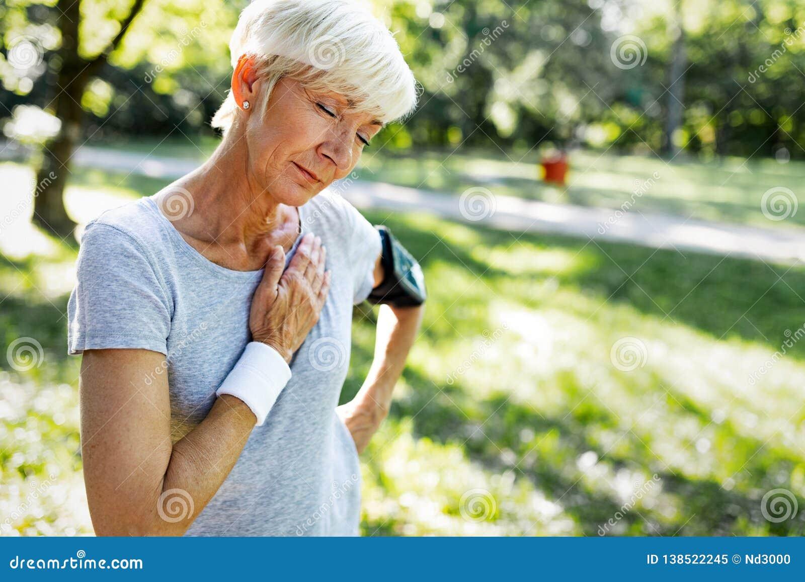Mujer mayor con el sufrimiento del dolor de pecho del ataque del corazón durante activar