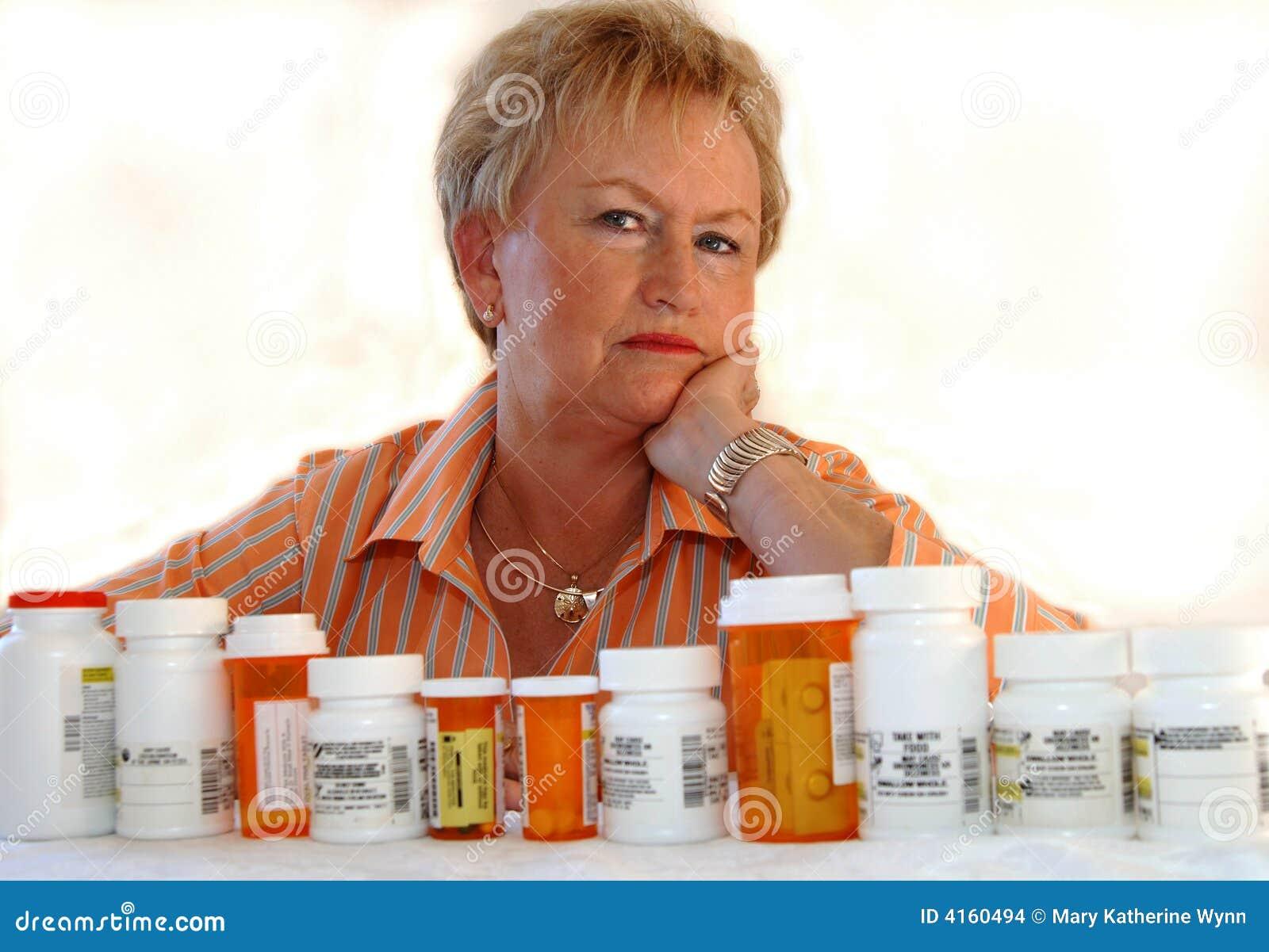 Mujer mayor con las botellas de la medicina