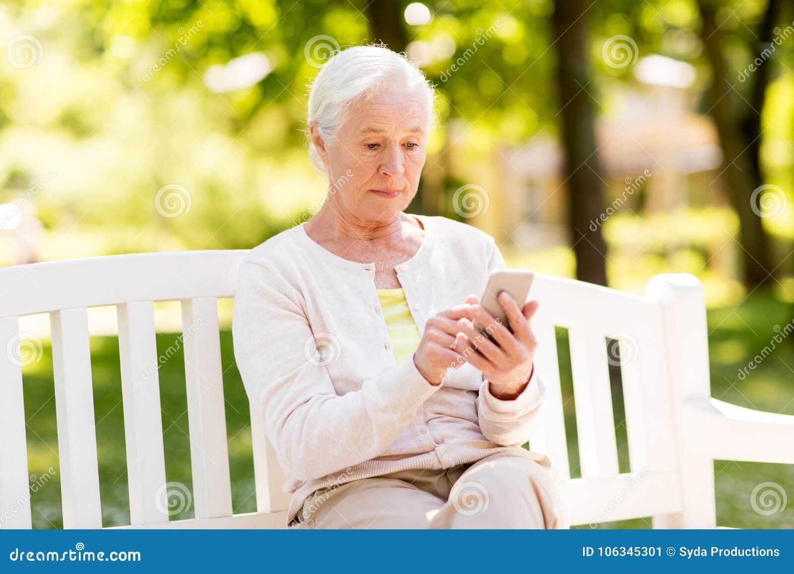 Mujer mayor con smartphone en el parque del verano