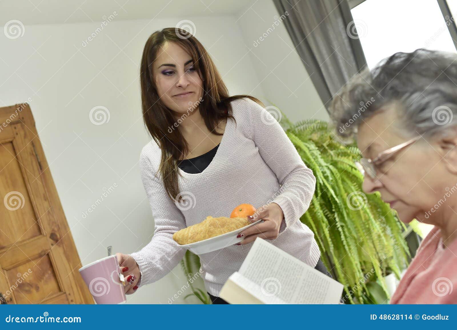 Mujer mayor con un desayuno casero de la porción del cuidador