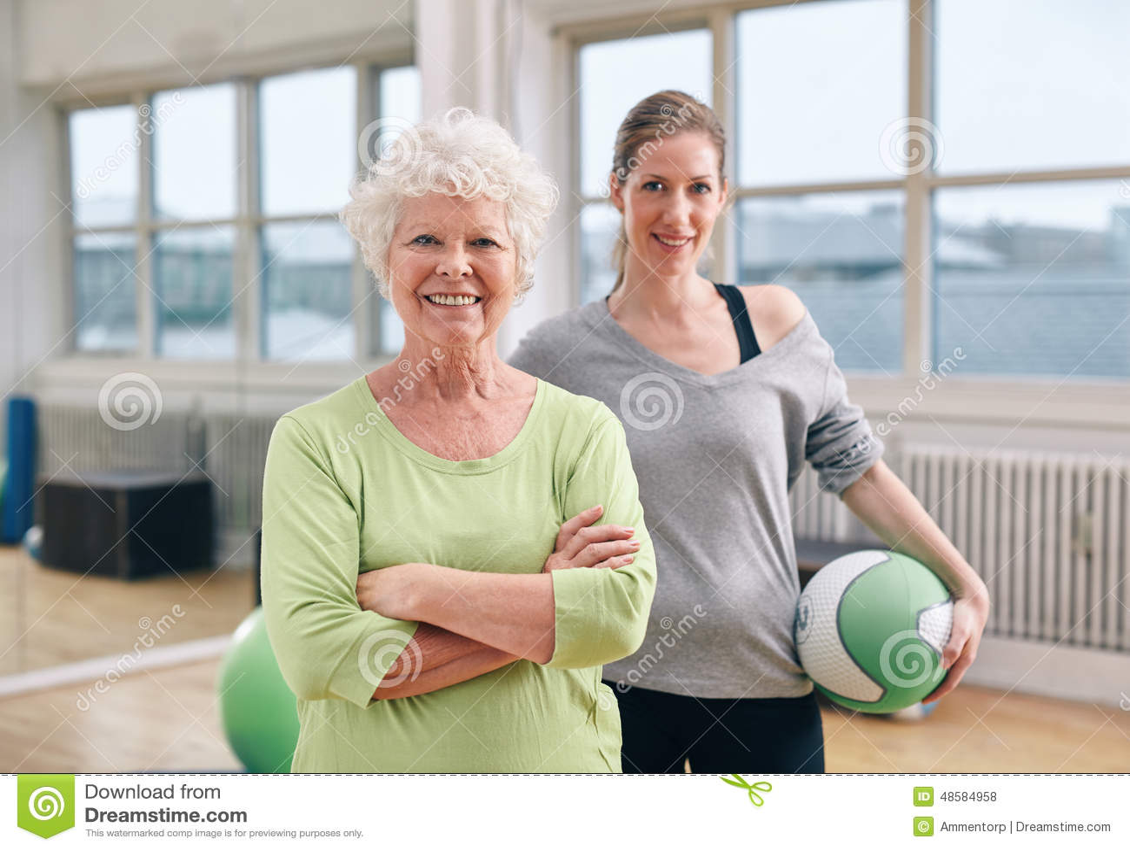 Mujer mayor en el club de salud con el instructor de gimnasio