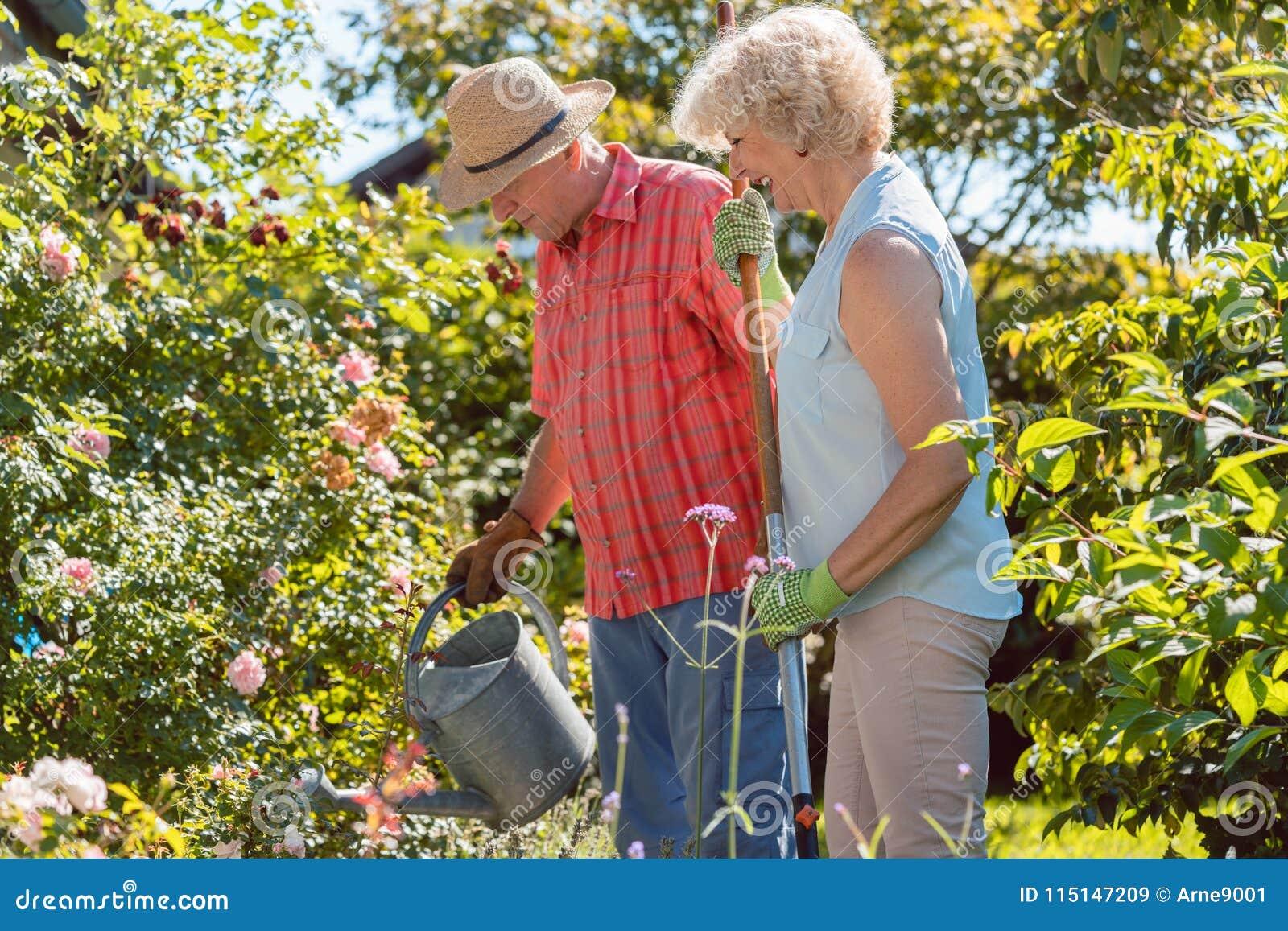Mujer mayor feliz activa que se coloca al lado de su marido durante trabajo del jardín