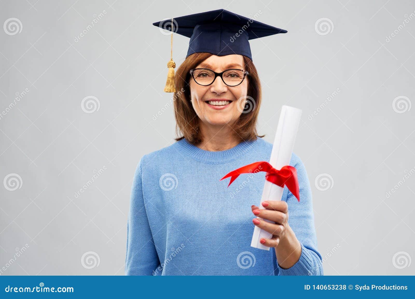 Mujer mayor feliz del estudiante de tercer ciclo con el diploma