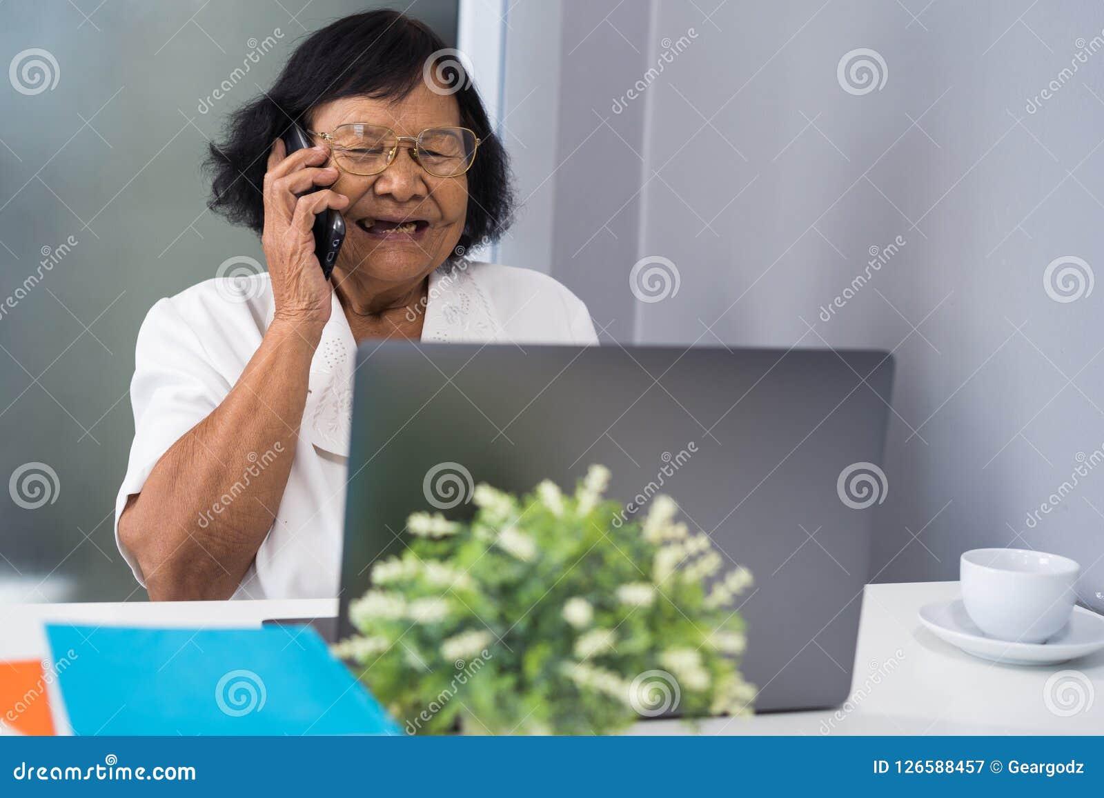 Mujer mayor feliz que habla en el teléfono móvil y que trabaja en el ordenador portátil