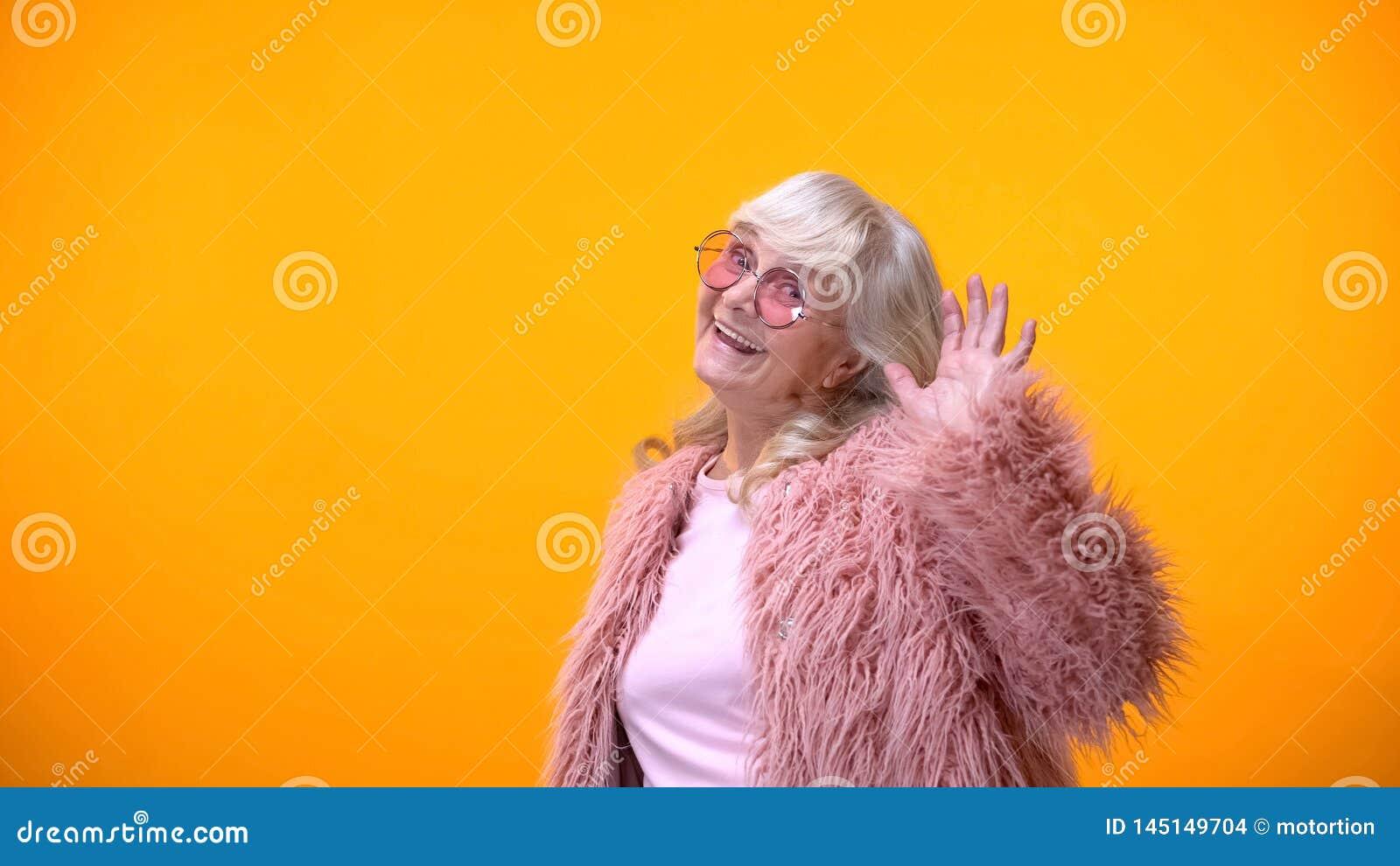 Mujer mayor infantil en capa rosada y gafas de sol redondas que sonríe en cámara