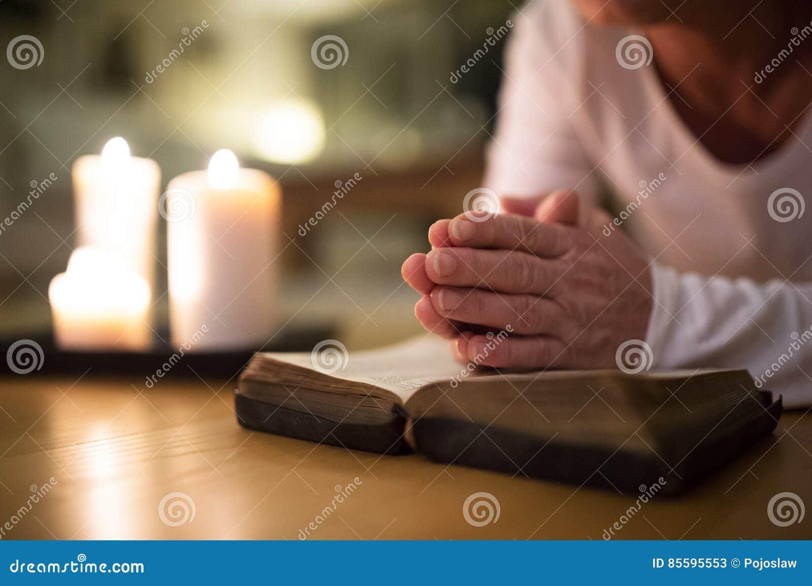Mujer mayor irreconocible que ruega, manos abrochadas juntas en h