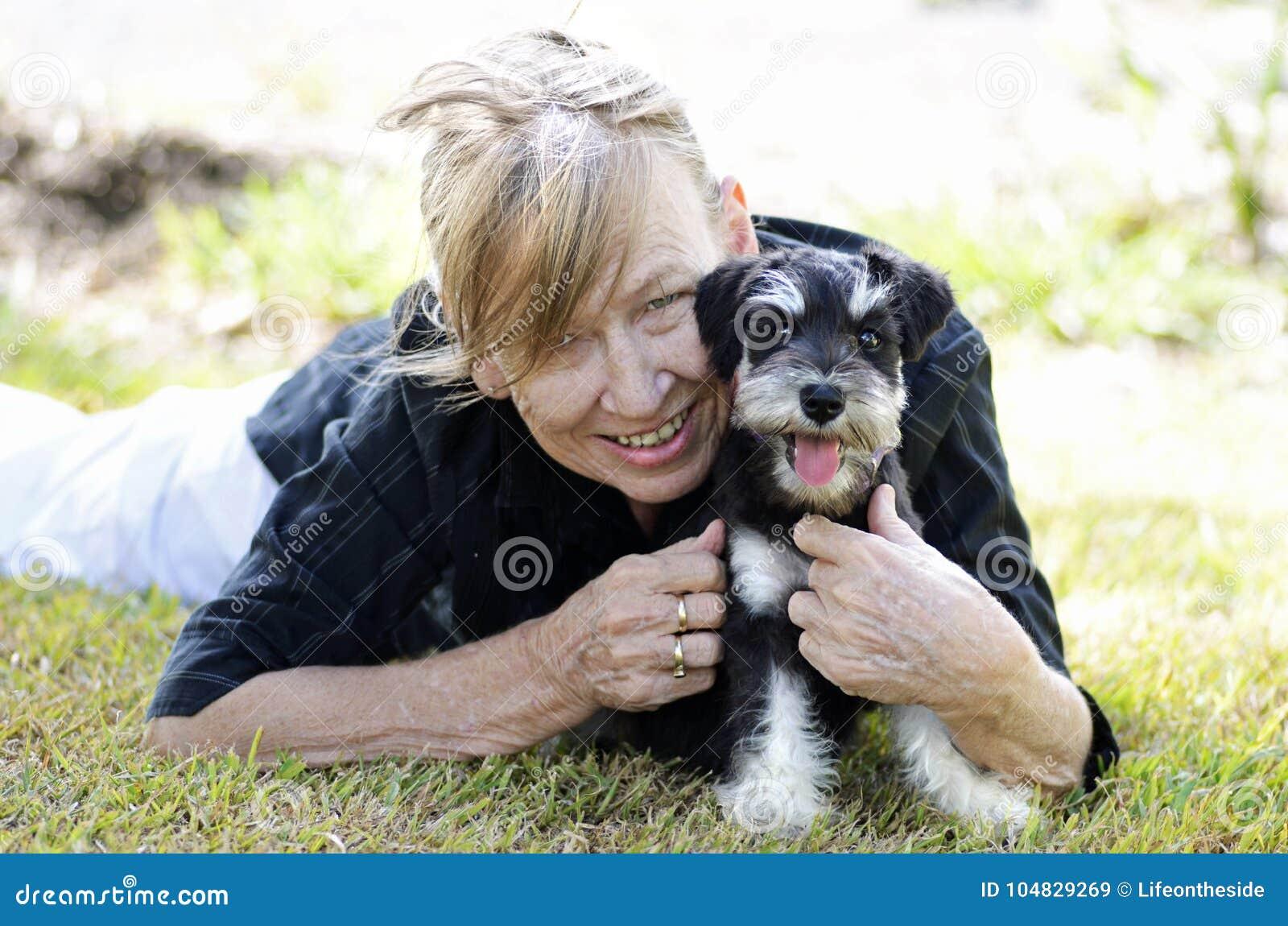 Mujer mayor madura feliz que sonríe abrazando el perro de perrito del animal doméstico