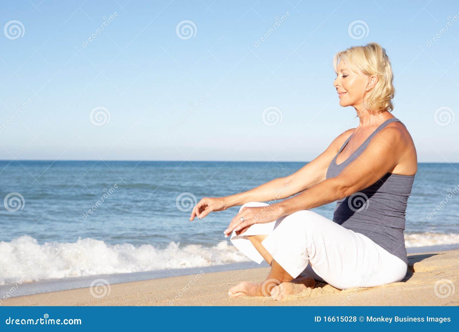 Mujer mayor Meditating en la playa